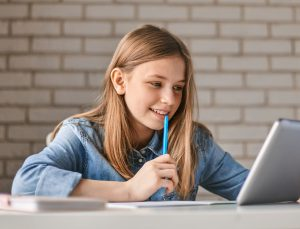Cute teen schoolgirl does her homework with a tablet at home. The child uses gadgets for learning